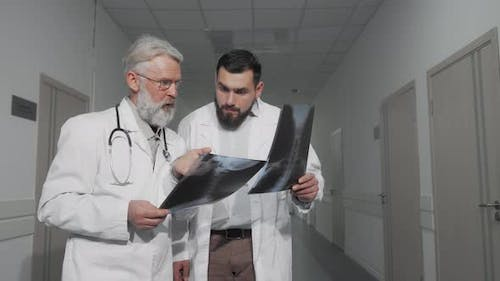 Two Doctors Talking in Hospital Hallway Examining Xray Scans Together