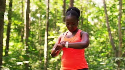 African Woman with Earphones and Smart Watch