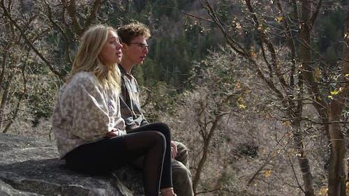 Young couple sitting on rock ledge