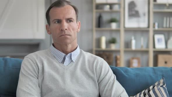 Thumbnail for Nachdenklicher Mann im mittleren Alter sitzt auf Couch im Kreativbüro