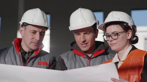 Construction Industry, Men and Woman in Glasses and Protective Helmets with Blueprints of New