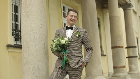 Thumbnail for Groom, Young Man Stay Near House with Columns with Wedding Bouquet. He Waiting for His Beloved Bride