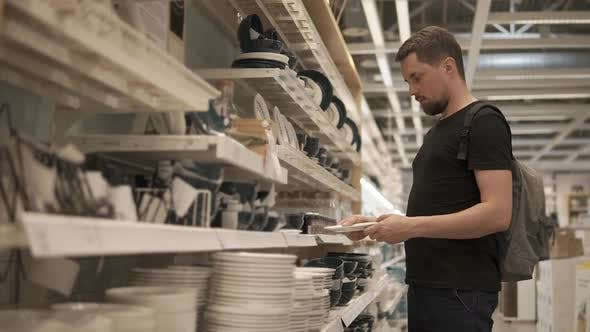 Man is Inspecting Ceramic Plates in Crockery Shop Taking and Putting Back