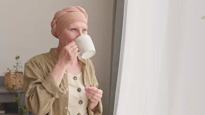Happy Woman in Headscarf Enjoying Tea at Home
