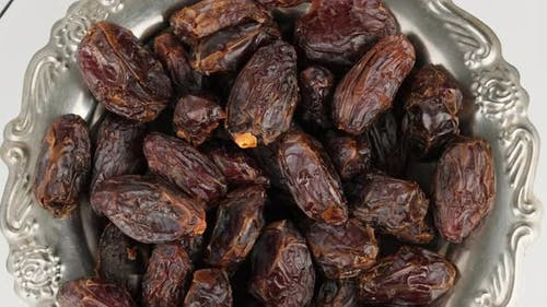 dried large dates on a metal plate that rotates