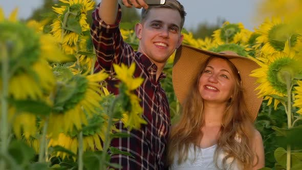 Thumbnail for Man and Pregnant Woman Make Selfie in a Sunflowers Field