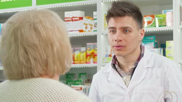 Thumbnail for Handsome Young Pharmacist Handing Shopping Bag with Purchase To a Customer
