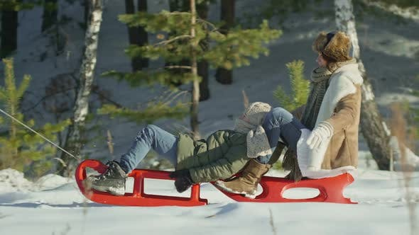 Cover Image for Happy Parents Pulling Sleds with Son