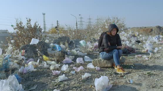 A Girl Sits in a Place Contaminated with Plastic Bags. The Scale of the Planet s Pollution