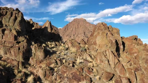 Thumbnail for Flying through gap on rocky mountain top viewing desert valley