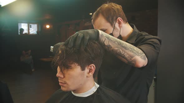 Cover Image for Tattooed Barber Cutting Out the Hair Edging on the Client with a Hair Trimmer