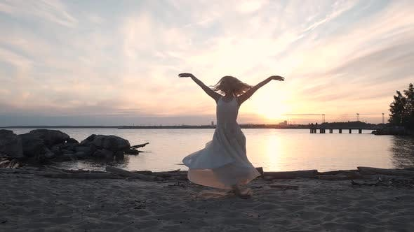 Cover Image for Girl Dancing and Spinning on the Beach at Sunset
