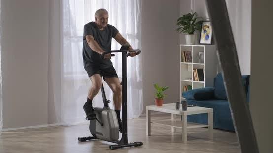 Sportliche Aktivität in der Heimat Der Mittlere Menschen verwendet stationäres Fahrrad im Wohnzimmer Gesunder Lebensstil