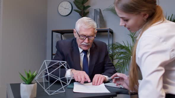 Senior Businessman Company Director Explaining Documents Discussing Project with Woman Colleague