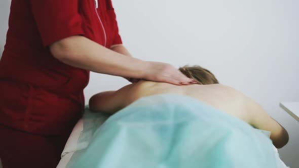 Massage Therapist Does Classical Procedure with Patient Back