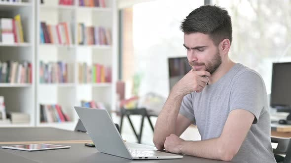 Thumbnail for Thoughtful Young Man Using Laptop in Office