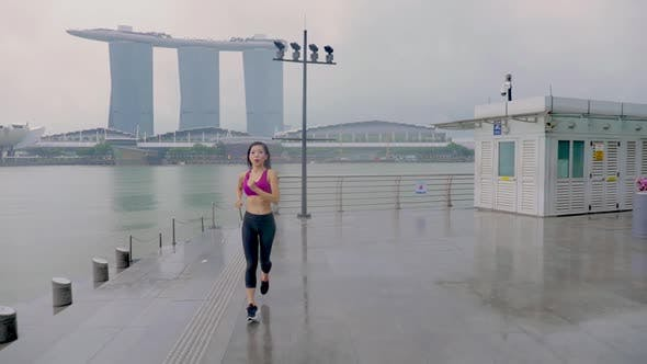 Thumbnail for Middle-aged Asian woman jogging in the rain in Singapore