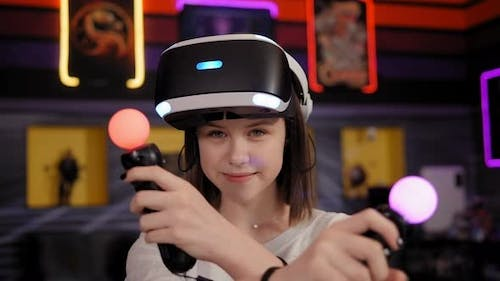 Teen Girl Wearing Virtual Reality Headset Holding Controllers in Hands