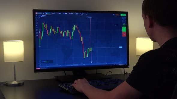 Thumbnail for A Man Sits at a Table and Looks at a Candle Chart on a Computer Screen