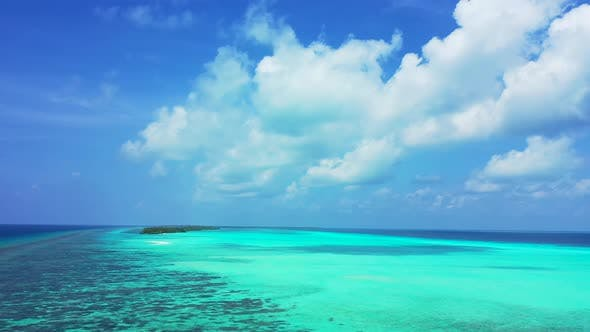 Daytime overhead travel shot of a paradise sunny white sand beach and aqua blue ocean background