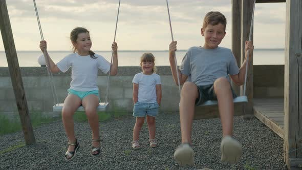 Thumbnail for Children Swing on a Swing in the Street at Sunset.