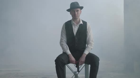Thumbnail for Handsome Confident Well-dressed Man in a Hat Sitting on the Chair Holding a Gun in the Smoky Room in