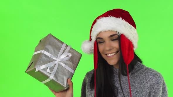 Thumbnail for Gorgeous Santa Claus Woman Smiling Holding Christmas Gift