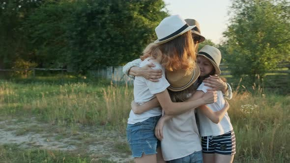 Cover Image for Happy Mother Hugging Children, Woman with Three Daughters in Nature