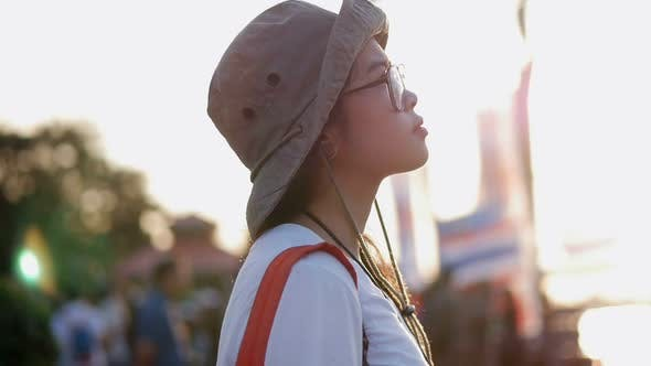 Young Asian woman looking around amusement park at sunset.