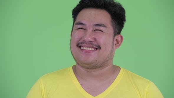 Thumbnail for Face of Happy Young Overweight Asian Man Thinking