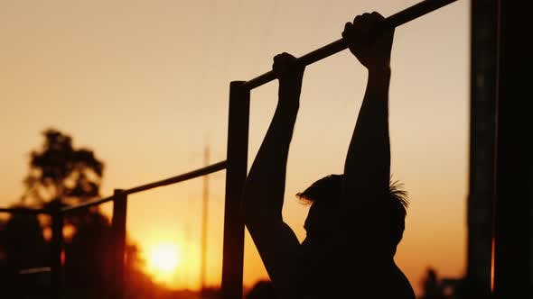 Cover Image for Teenage Boy Pulls Himself Up on a Horizontal Bar in the Yard