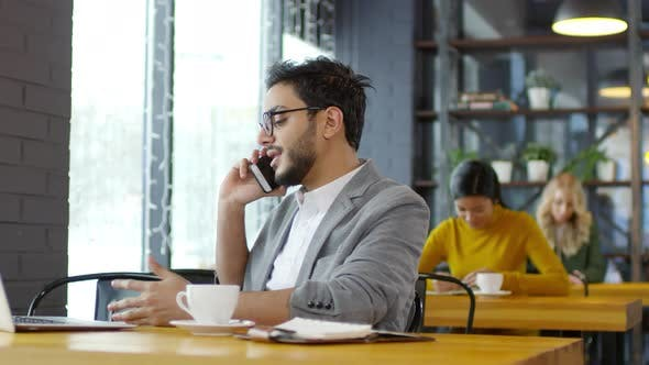 Thumbnail for Middle Eastern Businessman Speaking on Phone in Cafe
