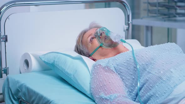 Retired Old Woman Breathing with Oxygen Mask