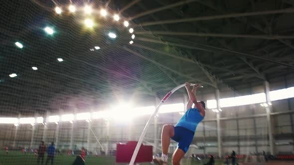 Thumbnail for Pole Vault Training in the Stadium - a Young Man in Blue Shirt Jumping Over the Bar