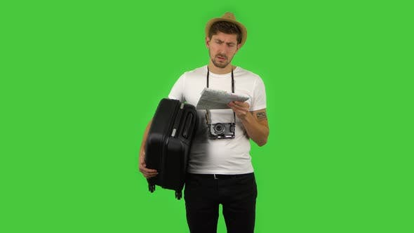 Cover Image for Tourist with Suitcase in Hand and Retro Camera Carefully Examines Map, Then Looking at Camera with