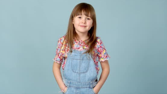Thumbnail for Cute Little Girl Standing in Dungarees Jeans with Hands in Pockets