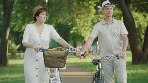 Positive Loving Mid-adult Man and Woman Walking with Bikes and Talking. Portrait of Caucasian