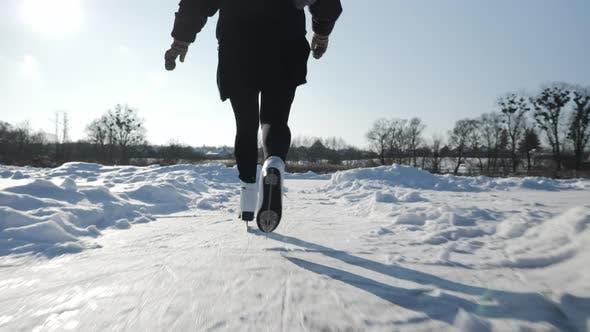 Thumbnail for Professional female skater in white figure skates is skating on frozen lake