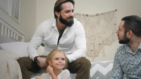 Same Sex Male Couple At Home. Fathers with daughter in bedroom