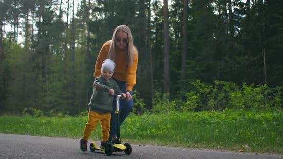Thumbnail for Eine junge Mutter und ihr Sohn lernen, einen Roller zu fahren. Muttertag. In einem Pinienwald auf der