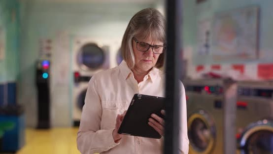 Mature white lady using portable wireless pad device while at laundromat