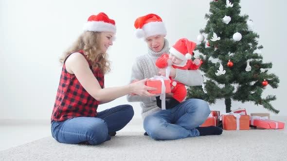 Thumbnail for Familienurlaub und Weihnachtskonzept. Junge Mutter und Vater mit einem Kind packen ein Weihnachten