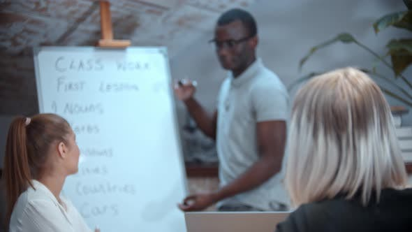 Thumbnail for English Lesson in the Class with an African American Teacher - Two Women Sitting By the Table and