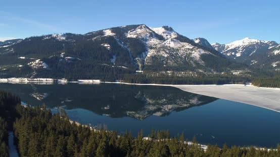 Frozen Lake Snow Melt Mountain Reflection Blue Water Reveal Interstate Highway 90 Road Aerial View