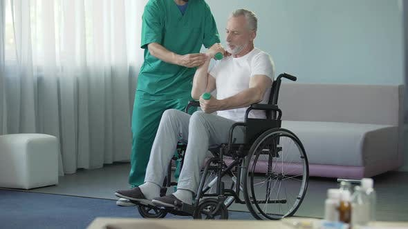 Thumbnail for Male in Wheelchair Pumping His Weak Muscles with Help of Nurse, Rehabilitation