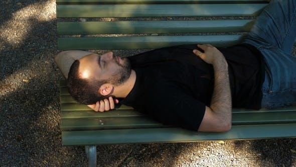Young man sleep on a bench.