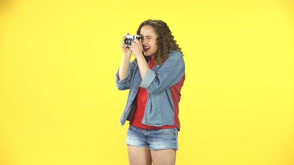 Smiling Girl Is Shooting Pictures on a Retro Photo Film Camera. Retro Style Vintage Picture Woman