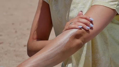 Woman Spreading Sunscreen on Her Arm at the Beach on a Hot Sunny Day