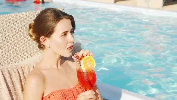 Thumbnail for Beautiful Happy Woman Enjoying Drinking Cocktail at the Poolside