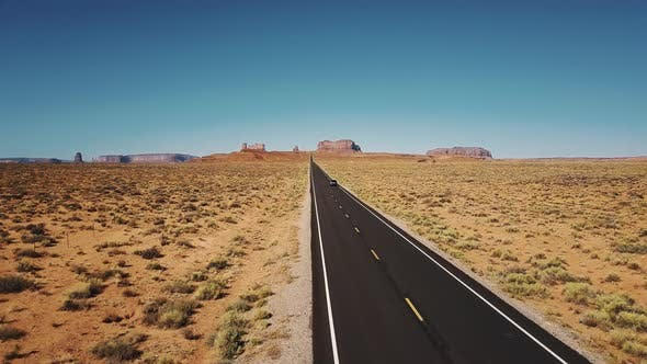 Thumbnail for Drone Follows Car Moving Along Iconic American Desert Highway Road in Monuments Valley with Big